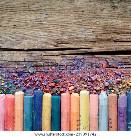 Artistic pastel crayons and pigment dust on old rustic wooden background. - stock photo