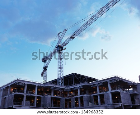 Artistic photo of a crane at a construction site at sunset over blue sky - stock photo