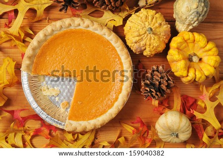 Artistic photo of a whole pumpkin or sweet potato pie with a slice missing - stock photo