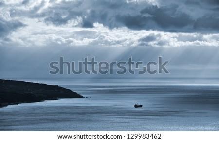 Artistic photo. Seascape. Lone transport ship in the sea. - stock photo