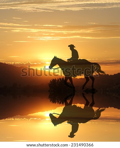 Artistic photography of a cowboy riding into the sunset with a mirror image of the horse and rider. - stock photo