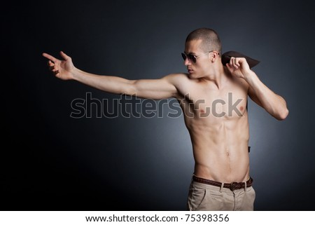 Artistic picture of a shirtless young male with sunglasses on a dark background - stock photo