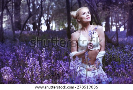Artistic portrait of a blonde woman in a bluebell forest - stock photo