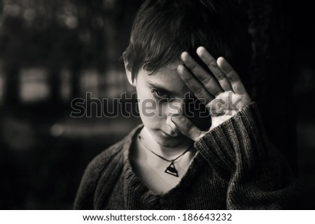 Artistic portrait of a boy child in the woods, loneliness - stock photo