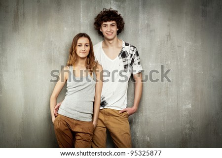 Artistic portrait of a young couple on a gray, textural background.