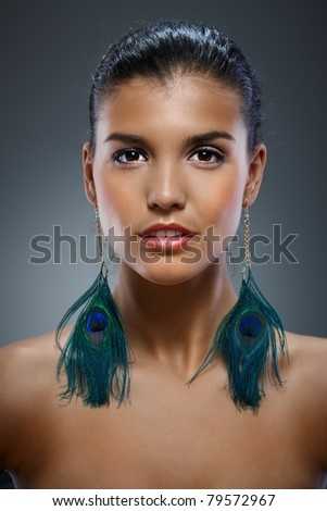 Artistic portrait of beautiful young woman with extraordinary earrings.? - stock photo