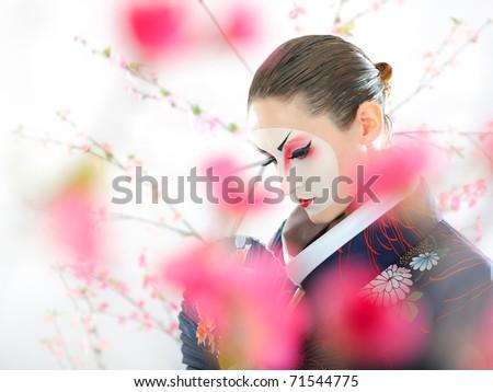Artistic portrait of japan geisha woman with creative make-up near sakura tree in kimono - stock photo