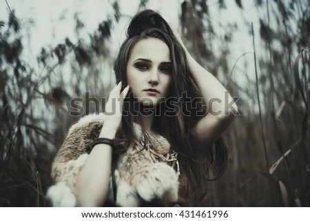 Artistic portrait of young beautiful woman in Indian style with fur on the field