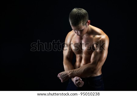 Artistic shot of a young man holding his hands as if being cuffed, dark background - stock photo