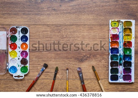 Artistic squirrel brush and water paints. Drawing tools for pupils, students, artists . Palette of twenty-four colors. Brushes and watercolor on warm wooden background, tools for art - stock photo