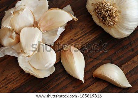 Artistic still life of garlic cloves (arranged to resemble flower petals) on rustic dark wood background.  Directional natural lighting for effect. - stock photo