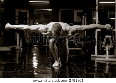 artistic training shot of young muscular man in the gym