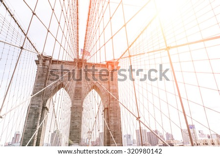 artistic view of the famous Brooklyn bridge in New York. Image taken on the upper part, with buildings skyline behind. concept about New york and traveling - stock photo