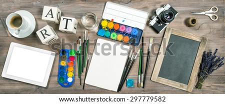 Artistic workplace mock up. Watercolor, brushes, digital tablet pc, chalkboard, vintage no name camera, office supplies, tolls and accessories. Retro style toned picture - stock photo