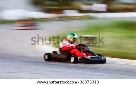 Artistically motion blurred image of a cart race. One cart has just negotiated a tough curve - stock photo