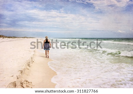 Artistically textured and toned photograph of an active mature woman viewed walking away from the camera on a beautiful sunny beach.