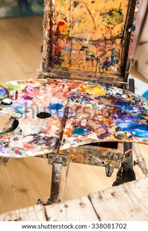 artists brush and oil paints on wooden palette  - stock photo