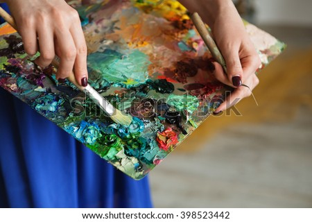 artists brushes and oil paints on wooden palette. macro artist's palette, texture mixed oil paints in different colors and saturation. palette with paintbrush and palette-knife hands.  - stock photo