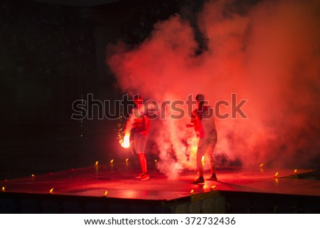 Artists juggling with two burning poi's at fire performance. The stage is covered with red smoke - stock photo