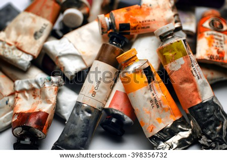 Artists paint tubes; used tubes of oil paints in box; differential focus  - stock photo