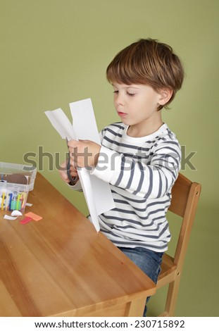 Arts and crafts activity, child learning to cut with scissors, learning and education concept - stock photo