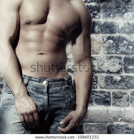 artwork male with a sexy man without a shirt standing against a wall - stock photo
