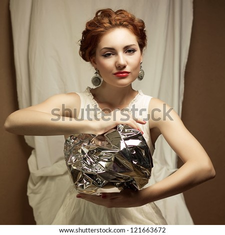 Arty portrait of a fashionable queen-like ginger model holding silver foil sphere over white curtain background. Studio shot - stock photo