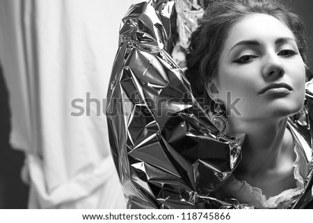 Arty portrait of a fashionable queen-like model with silver foil cape over white curtain background. close up. black and white studio shot - stock photo