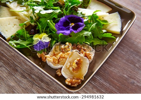 Arugula mediterranean salad with goat cheese honey flowers and nuts - stock photo