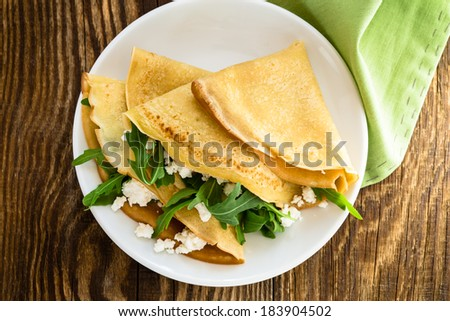 Arugula salad and cheese crepes for healthy breakfast viewed from above