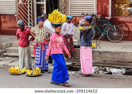 Arusha, Tanzania, Africa - January 2, 2013: A woman walks on her head carrying a bunch of bananas - stock photo