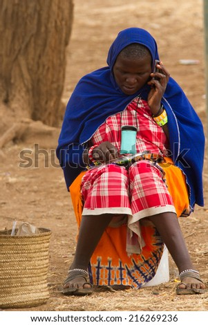 ARUSHA, TANZANIA - AUGUST 18: Masai woman while using a mobile phone, masai people still live in the old way but with a slight use of technology august 18, 2014 in Arusha, Tanzania - stock photo