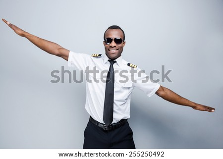 As a plane. Happy African pilot in uniform gesturing and smiling while standing against grey background - stock photo