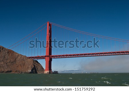 As fog drifts in from the Pacific Ocean to cover San Francisco the Golden Gate bridge slowly disappears.  The bridge is one of the city's most iconic sites. - stock photo