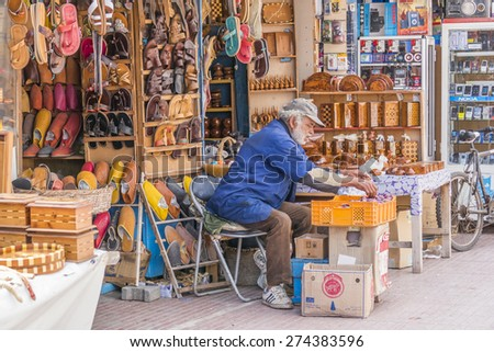 AS-SAWIRA, MOROCCO, APRIL 7, 2015: Seller of leather shoes and other souvenirs sits in front of his stand - stock photo