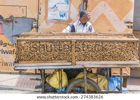 AS-SAWIRA, MOROCCO, APRIL 7, 2015: Seller of peanuts transports his mobile stand - stock photo