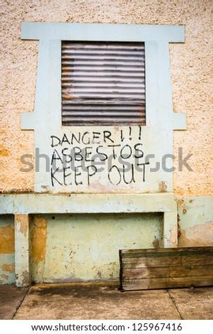 Asbestos warning on abandoned factory - stock photo