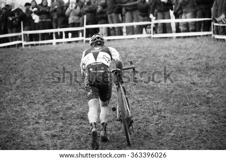 ASHEVILLE, NORTH CAROLINA � JANUARY 10: An elite racer pushes his bike up a muddy hill at the cyclocross nationals on January 10, 2016 in Asheville, North Carolina - stock photo