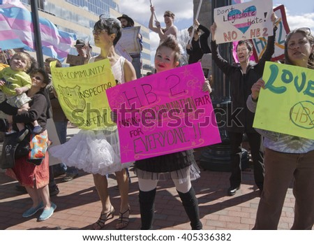Asheville, North Carolina, USA - April 2, 2016: Crowd holds signs, waves symbolic flags, and protests the new North Carolina HB2 Law that restricts rights to those who are gay or transgender