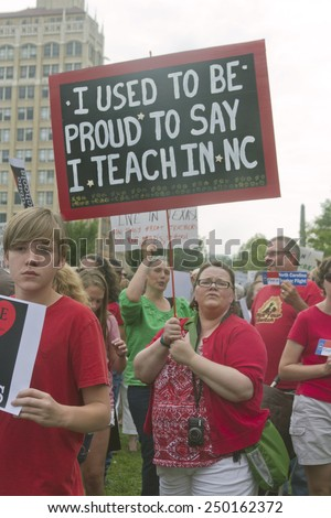 Asheville, North Carolina, USA - August 4, 2014: A teacher and others hold signs protesting the state of public education in North Carolina and in America at a Moral Monday rally in Asheville, NC - stock photo