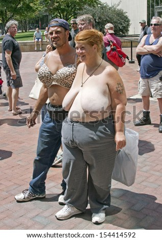 ASHEVILLE, NORTH CAROLINA, USA - AUGUST 25, 2013: A topless woman and a man wearing a bra supports the right of both men and women to go shirtless in public at the Go Topless Rally in Asheville    - stock photo