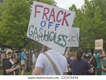 Asheville, North Carolina, USA - August 4, 2014: Man at a Moral Monday rally holds a sign protesting fracking amid a crowd of other protesters on August 4, 2014 in downtown Asheville, NC - stock photo