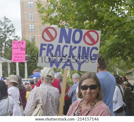 Asheville, North Carolina, USA - August 4, 2014:  Woman at a Moral Monday rally holds a sign protesting fracking amid a gathering crowd of demonstrators on August 4, 2014 in downtown Asheville, NC   - stock photo