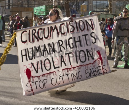 "Asheville, North Carolina, USA - February 7, 2016: Costumed young woman holds large sign saying ""circumcision is a human rights violation"" in the Mardi Gras parade"