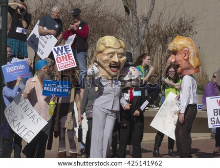 Asheville, North Carolina, USA - February 28, 2016:  Effigies of Hillary Clinton and Mr. Monopoly cozy up holding moneybags as Donald Trump watches and Bernie Sanders supporters hold signs