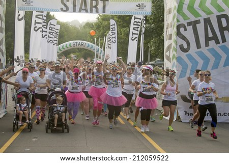 Asheville, North Carolina, USA - July 26, 2014: Color Run Runners in colorful outfits burst enthusiastically from the starting line as they begin the race on July 26, 2014 in downtown Asheville, NC - stock photo