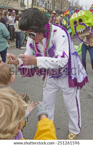 Asheville, North Carolina, USA - March 2, 2014:  A colorful costumed Elvis character gives Mardi Gras beads to a young girl in the Spring Mardi Gras parade on March 2, 2014 in downtown Ashevile, NC  - stock photo