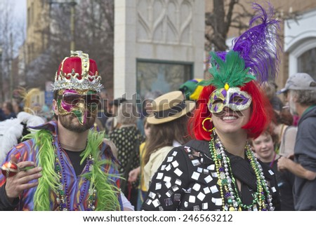 Asheville, North Carolina, USA - March 2, 2014:  A man and woman wear costumes and colorful masks as they walk in the Mardi Gras parade in downtown Ashevile, NC  - stock photo