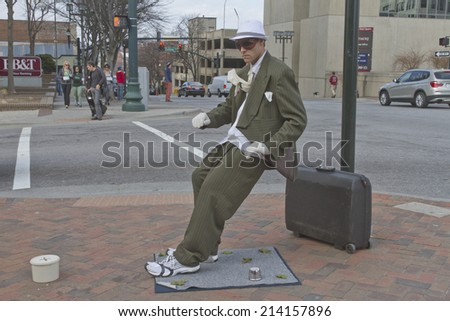 Asheville, North Carolina, USA - March 2, 2014: Living statue street busker leans at an impossible angle and remains completely immobile on March 2, 2014 in downtown Asheville, NC  - stock photo