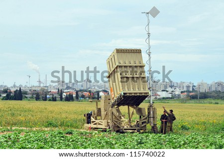 ASHKELON-APRIL 14:Israeli soldier near Iron Dome that  deployed on April 14 2011 in Ashkelon,Israel.The $200 million anti-rocket system was created by Israel against rocket attacks from the Gaza strip - stock photo